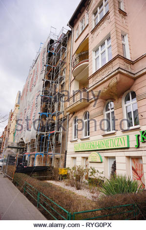 Poznan, Poland - March 8, 2019: JK hairdresser and beauty salon next to a building under construction on the Slowackiego street in the city center. - Stock Image