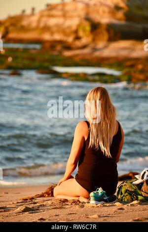 Young, blonde woman sitting and meditating on beach at sunset, at Sunset Cliffs Natural Park, Point Loma, San Diego, California, USA - Stock Image