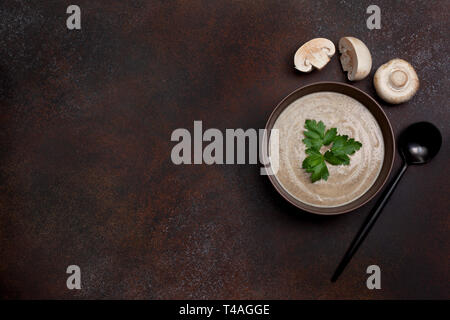 mushroom soup in a brown bowl, champignons on a brown background. view from above. copy space - Stock Image