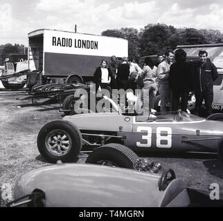 1960s, historical, motor racing at Crystal Palace race circuit in South London, London, England, UK. Cars parked on the grass by delivery trucks, one sponsored by Radio London. - Stock Image