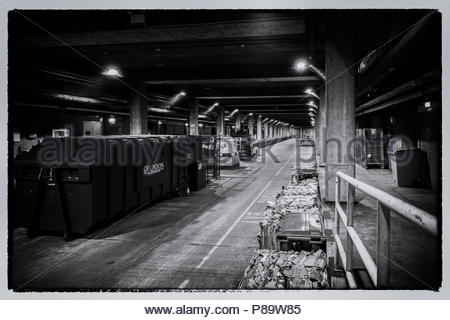 A monochrome image of the service road for deliveries beneath a UK shopping mall, a compactor and bales of crushed cardboard for recycling. - Stock Image