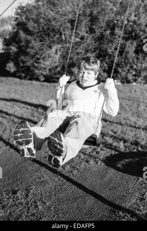 Boy on a swing in a Playground in Daventry during the winter - Stock Image