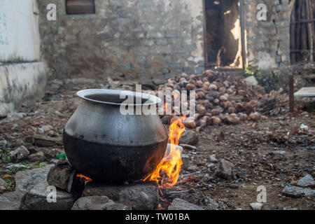 A big pot of water being boiled over an open fire - Stock Image