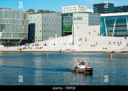 Oslo Norway, view of young people sailing a boat past the Oslo Opera House and the city's Barcode district on a summer afternoon, Norway. - Stock Image