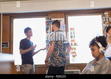 Creative designers brainstorming, reviewing photograph proofs in office - Stock Image