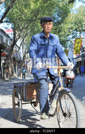 Tongli, China-November 28, 2008: Old man riding a tricycle in the shopping area of the town - Stock Image
