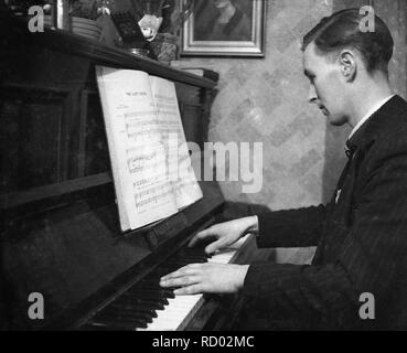 1950s, historical, at home, a man in a suit playing ''The Lost Chord' on a  piano, England, UK - Stock Image