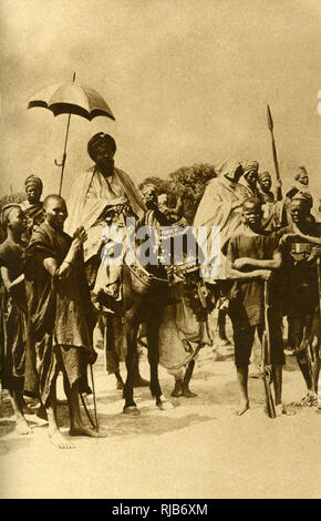 Emir of Gombe, Nigeria, West Africa, on horseback at a Durbar, shaded from the sun by a parasol held by a footman. - Stock Image