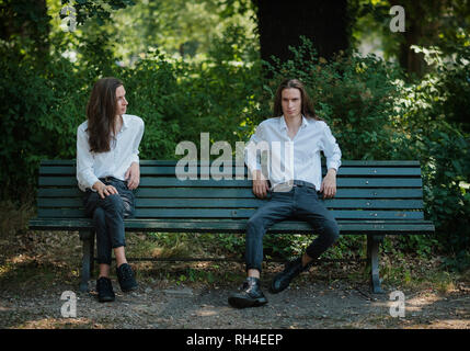 Multiple image man sitting on park bench with legs crossed and legs apart - Stock Image