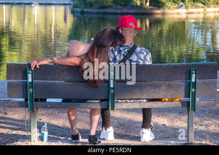 A girl  rests her head on her boyfriends shoulder whilst sitting on a park bench in a park in London - Stock Image