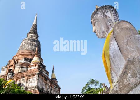 Buddha statue and ancient pagoda on blue sky background at Wat Yai Chaimongkol temple in Phra Nakhon Si Ayutthaya - Stock Image