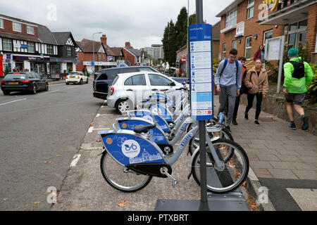Young people walking home from school past a row of nextbike bikes parked in the street in Llanishen village Cardiff Wales UK  KATHY DEWITT - Stock Image