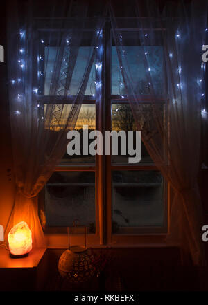 Decorative Himalayan Salt lamp turned on by old white wooden window with white net fabric curtains, looking out the wooden frames window sun setting o - Stock Image