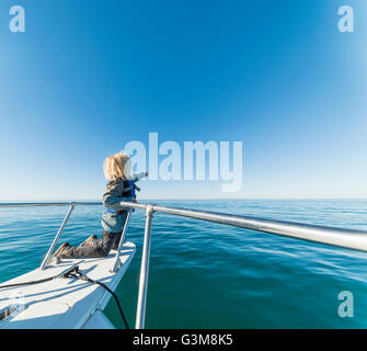 Boy kneeling on ships bow of sailboat looking away pointing - Stock Image