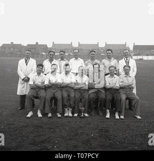 1950s, group photo for a works cricket team with trophy, England, UK. - Stock Image