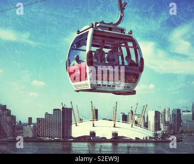 A cable car pod travels over the O2 Arena and the River Thames in London, England. This public transport system forms part of the London Underground network system. Photo © COLIN HOSKINS. - Stock Image