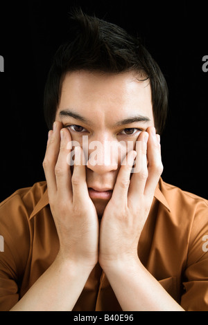 Portrait of Asian young man with hands on face - Stock Image