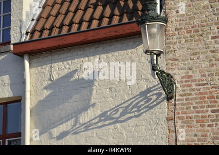 A traditional light post and its shadow on a Flemish style building in Bruges, Belgium - Stock Image