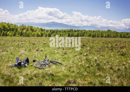 Man lying down by bicycle on grassy field against cloudy sky - Stock Image