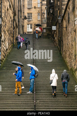 Tourists with umbrellas in rain walking up long steep steps in alley, Warriston's Close, Cockburn Street to Royal Mile, Edinburgh, Scotland, UK - Stock Image