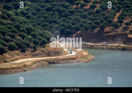Crete, Greece. June 2019. A trail of vehicles on safari around the dirt road of the Aposlemi Dam in central Crete - Stock Image