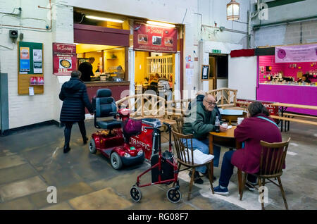 Disabled customers with Mobility Aids enjoying refreshment at the cafe in the Darlington Victorian Covered Market - Stock Image