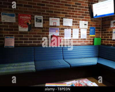 An empty waiting room & advice posters on the way seen in an NHS local doctors surgery waiting room in Warwickshire, UK, On May 14, 2019. - Stock Image