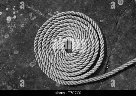 Coiled rope on flagstone. - Stock Image