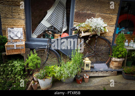 70th Birthday card picture with beautiful still life featuring an old bicycle, potted plants and trinkets and stone wall; - Stock Image