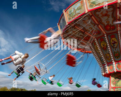 The motion of people on a fairground ride on a summer's day - Stock Image