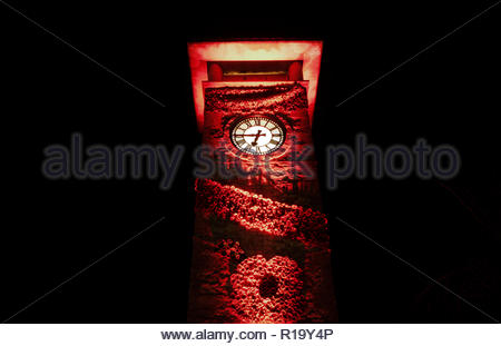 Gloucestershire, UK. 10th November 2018. 7000 knitted poppies have been produced by local residents in the Cotswold town of Nailsworth, adorning the Nailsworth War Memorial Clock Tower (built in 1951) and a nearby tree. The red lighting illuminates the display that commemorates a 100 years since the end of the First World War. Photo Phil Wills/Alamy Live News. - Stock Image