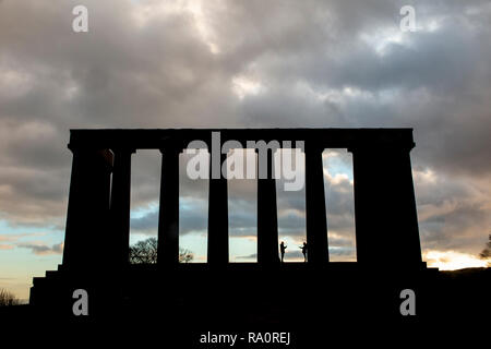 Dawn at The National Monument on Carlton Hill in Edinburgh city centre, with silhouettes of people enjoying the dramatic weather - Stock Image