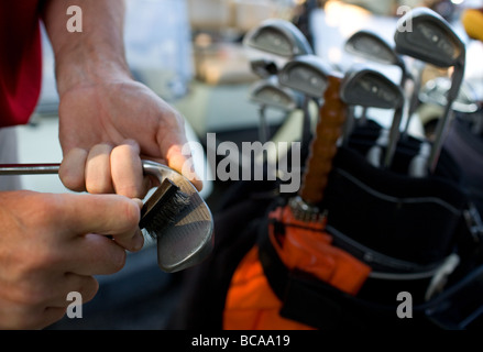 A man using a brush to clean his golf clubs before a round of golf. - Stock Image