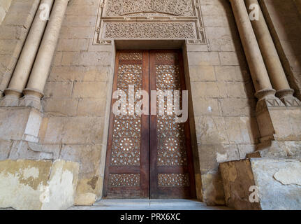 External old decorated bricks stone wall with arabesque decorated wooden door framed by stone ornate cylindrical columns leading to al Rifai Mosque, O - Stock Image