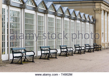 A row of empty seats in the botanical gardens in Sheffield, South Yorkshire, England, UK, one of the many green spaces in the industrial city. - Stock Image