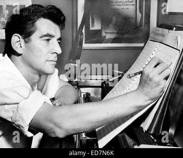 Leonard Bernstein, seated at piano, making annotations to musical score. 1955 - Stock Image
