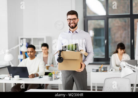 happy male office worker with personal stuff - Stock Image