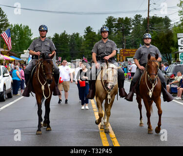 Three New York State Police officers riding horses in the 4th of July parade in Speculator, NY USA - Stock Image