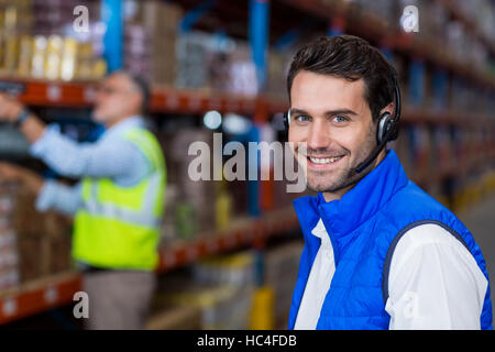 Warehouse worker in headset - Stock Image