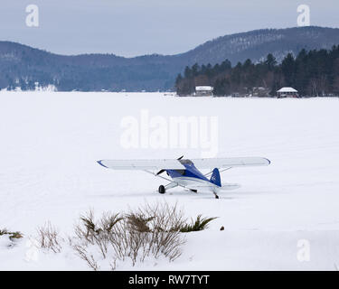 An experimental Carbon Cub model of the Piper Cub airplane on skis parked on the snow and ice on Lake Pleasant, NY USA - Stock Image