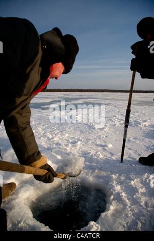 Russia, Siberia, Baikal; Russia, Siberia, Baikal; Undergoing preparations for fishing on frozen lake baikal in winter - Stock Image
