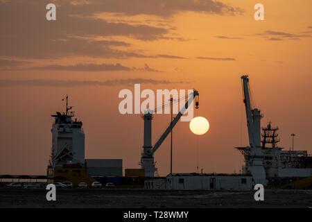 Lifting Crane mounted on Cargo ship during sunset - Stock Image