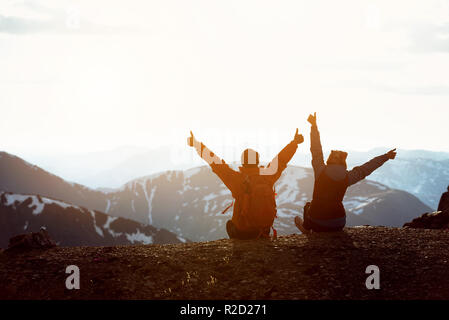 Two happy hikers sits on mountain top with raised arms and having fun - Stock Image