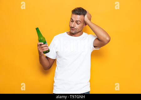 Image of drunk man 30s in white t-shirt holding bottle and drinking beer while standing isolated over yellow background - Stock Image