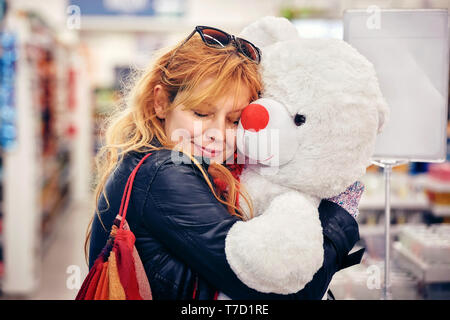 Young attractive hipster female smiling and  hugging a big white teddy bear at the shop. Concept of valentine's day birthday present. - Stock Image