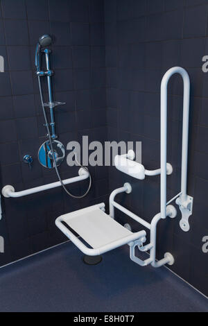 Disabled shower in wet room with hand rails and seat in down position. - Stock Image