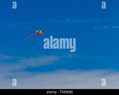 A kite flying in the air against a beautiful blue summer sky. - Stock Image