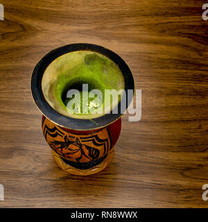 A gourd container (cuia) filled with green mate to make the Brazilian traditional   chimarrao on wooden table against, top side view - Stock Image