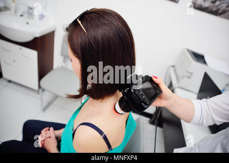 the doctor examines the patient's mole - Stock Image