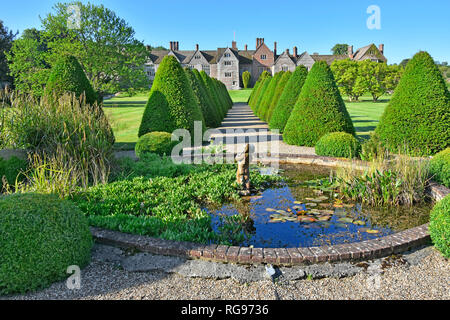 Elizabethan rural garden topiary & path with pond in historic parkland & gardens rows of repeat conifers Littlecote House beyond Wiltshire England UK - Stock Image